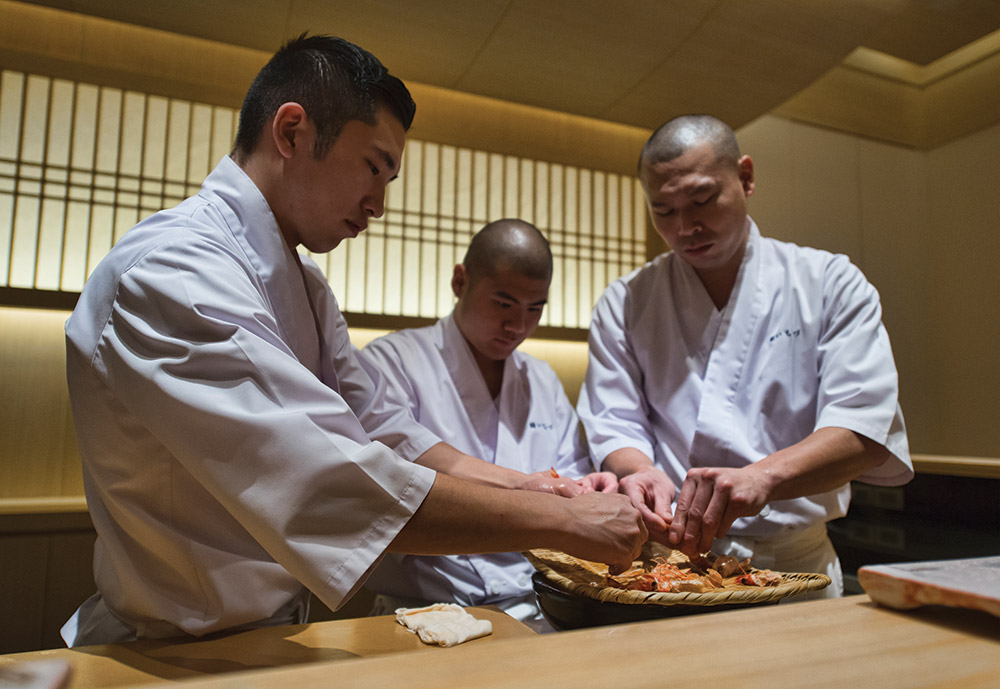 Master sushi Chef Riku Toda, left, and his apprentices at work