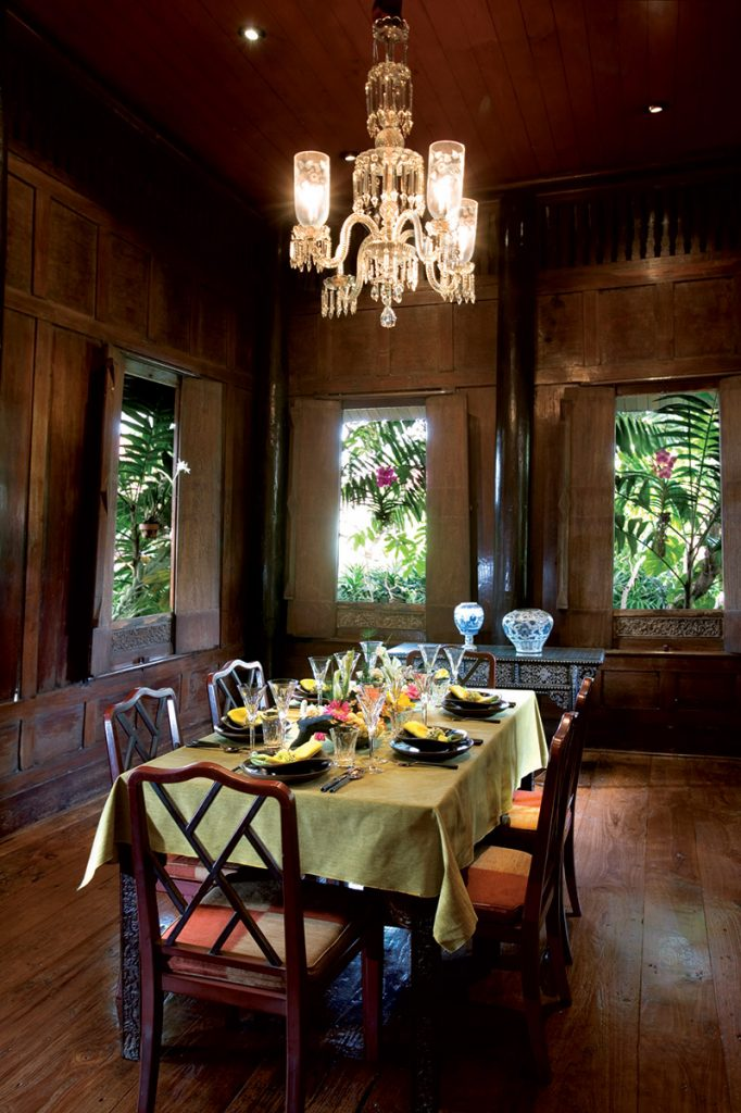 The dining room with a dining table, silverware and a chandelier.