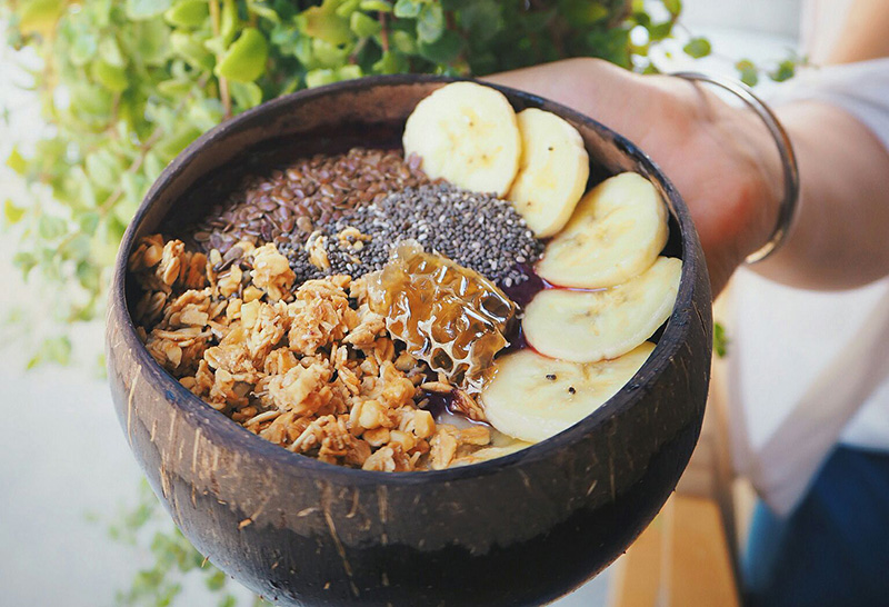 A customized bowl topped with bananas, chia seeds, bee pollen, and granola