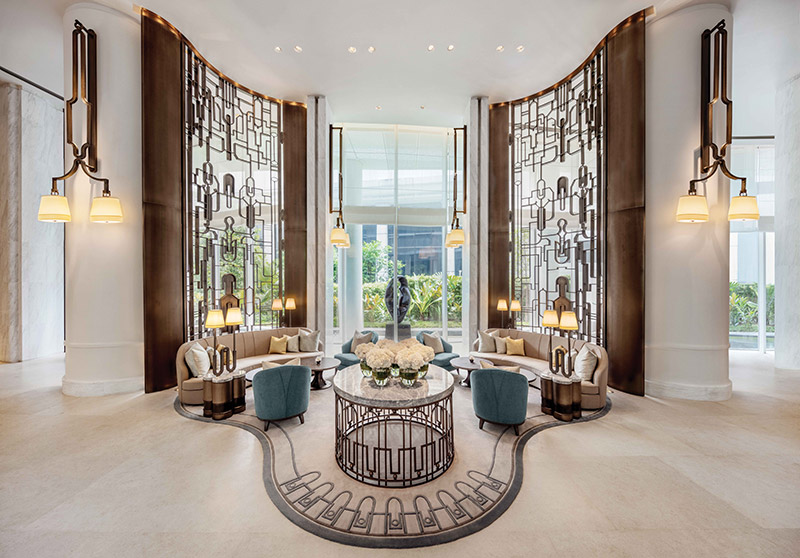 Waldorf Astoria Bangkok's lush lobby with white and matte gold color tones